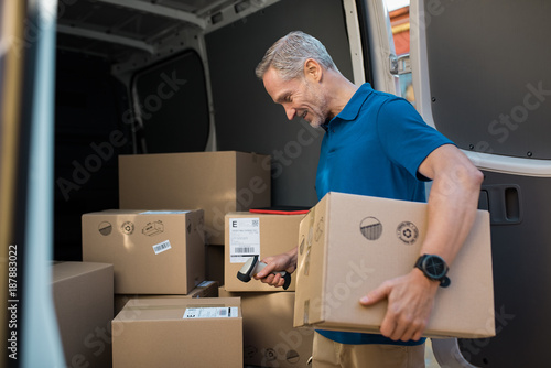 Fotografía  Deliveryman scanning parcel barcode