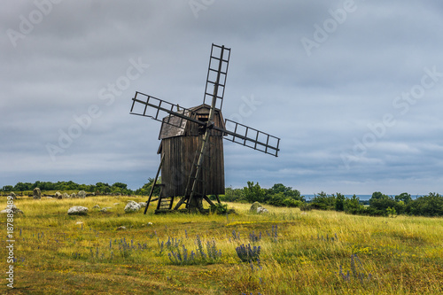Old wooden windmill standing on a green field by the coast