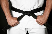 Closeup Of Male Karate Or Ju-jitsu Fighter Hands In White Kimono And Black Belt
