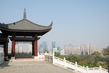 A Traditional Wooden Asian Gazebo With Foshan Cityscape In The Background