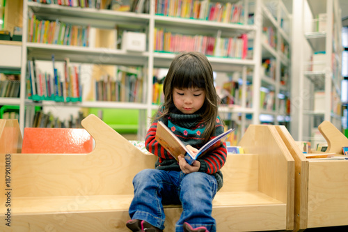 Canvastavla little girl reading a book in a library