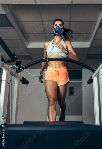 Fotografía Runner with mask on treadmill in sports science laboratory