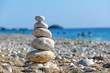 Stones balance on beach, people sunbathe, swim and enjoy on sea vacation