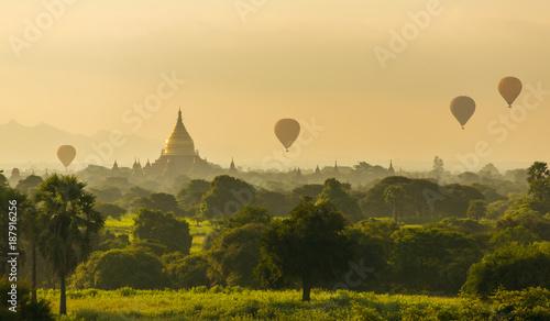 Fotobehang Zwavel geel Air balloons over Buddhist temples at sunrise in Bagan, Myanmar.