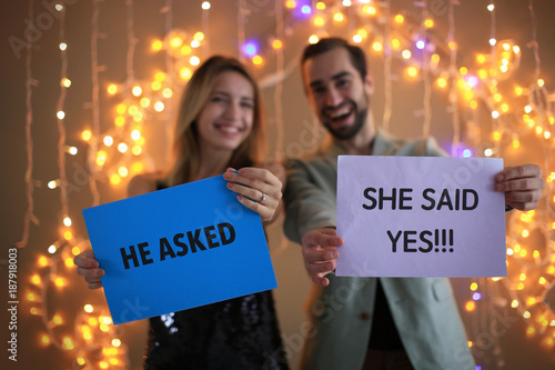 Happy couple holding papers with text HE ASKED and SHE SAID YES against blurred Canvas Print