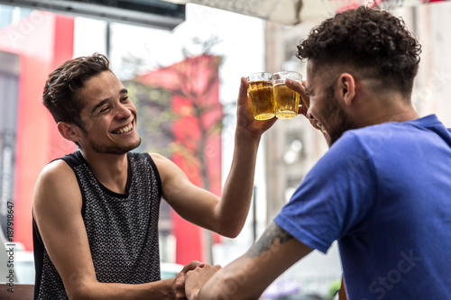 Fototapeta Homosexual Couple Raising a Toast with Beer in Bar