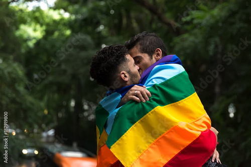 Fotografia  Gay Couple Kissing with Rainbow Flag in the Park