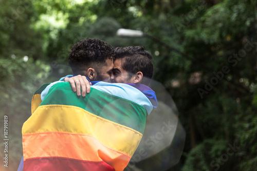 Fotografía  Gay Couple Kissing with Rainbow Flag in the Park