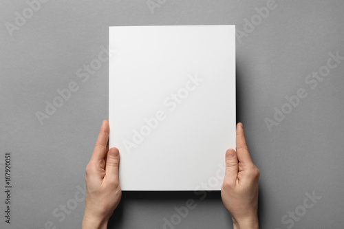 Fotografering  Woman holding brochure with blank cover on grey background
