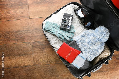 9ff5c79b212 Open suitcase with warm clothes and documents on wooden floor. Winter  vacation concept