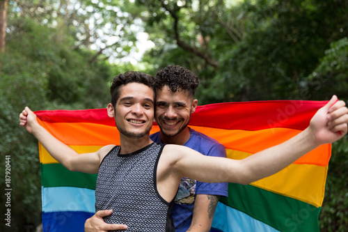 Fotografía  Gay Couple Celebrating with Rainbow Flag in the Park