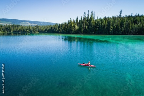 Woman kayaking in shallow turquoise water along the sea