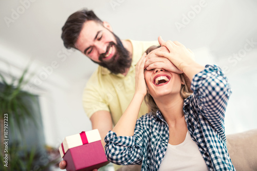 Smiling young man surprising cheerful woman with a gift box at home Fototapet