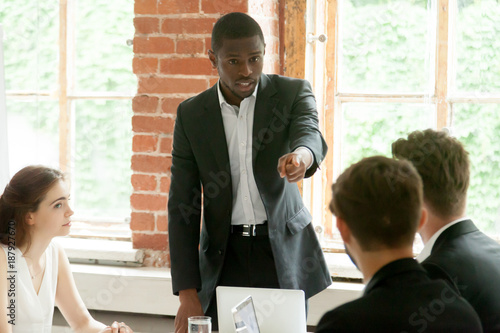 Canvastavla  Rude impolite african businessman pointing finger at colleague on team meeting,