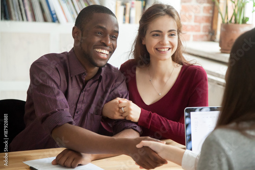 Valokuva Smiling multiracial couple customers shaking hands with mortgage broker or finan