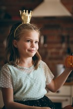 Cute Girl With A Crown Holding Pumpkin In Kitchen