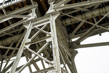 A Bridge Over A River Built From A Truss. Bridge, Truss Joined By Rivets In Old Technology On The River.