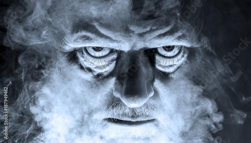 Fotografía das Porträt eines dämonisch aussehenden Mannes, umgeben von Nebel