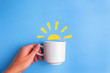 canvas print picture - sun and white cup on blue background