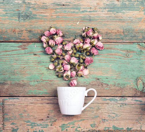 Coffee cup with heart from pink rose flowers coming out of it on old  turquoise wooden background. Top view. Flowers composition.