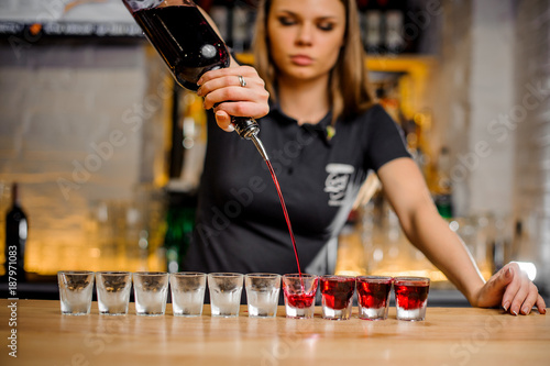 Photo professional barmaid pours alcohol into stacks that are lined up