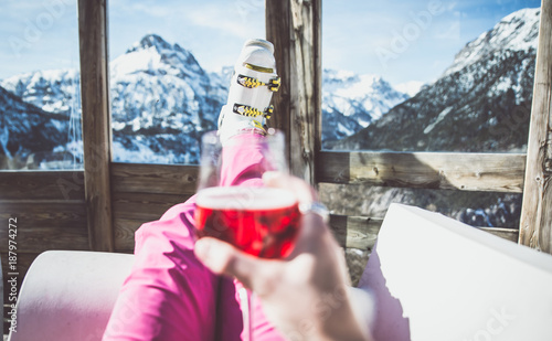 woman relaxing with a glass of wine and enjoying the mountain landscape