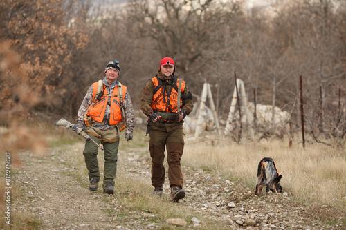 Valokuvatapetti hunters with dogs hunting a bird woodcock