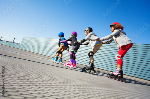 Happy preteen kids having fun while rollerblading