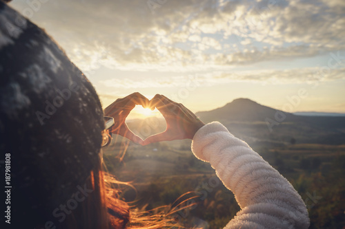 Платно Young woman traveler making heart shape symbol at sunrise