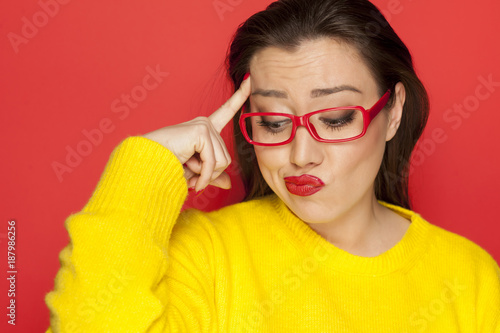 Fotografiet beautiful wondering woman with red glasses on red background