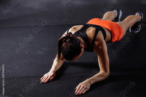 Obraz na płótnie young beautiful woman in sportswear doing plank while trainnig at cross fit gym