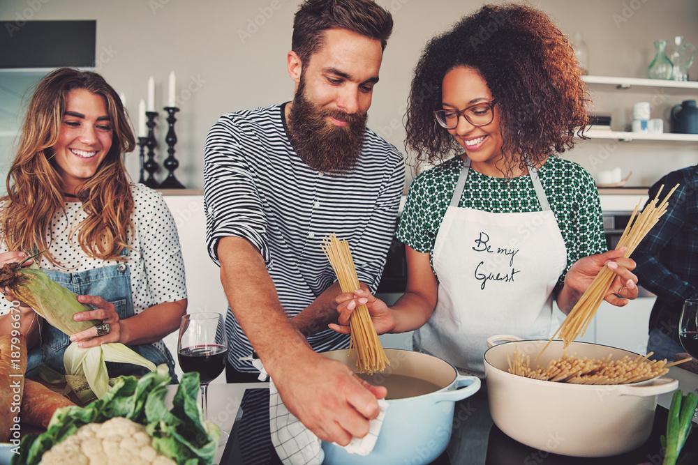 Fototapety, obrazy: Three friends cooking spaghetti