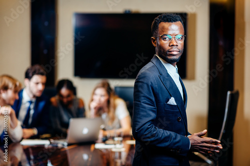 Fototapety, obrazy: handsome african businessman looking on camera with group of businesspeople on background