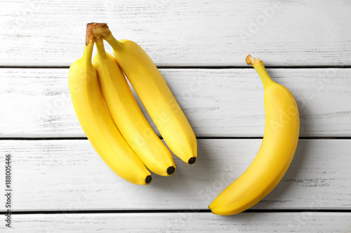 Tasty ripe bananas on white wooden background