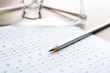 Exam form, pencil and student's eyeglasses, closeup
