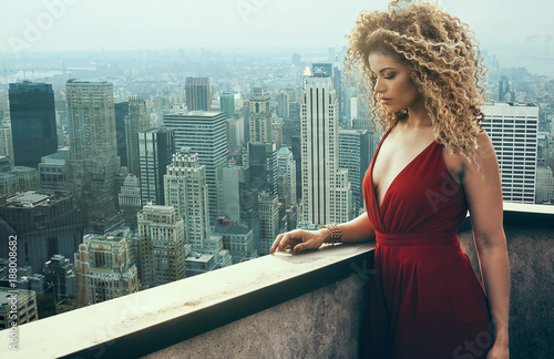 obraz PCV Beautiful and pensive woman portrait wearing red dress and New York cityscape