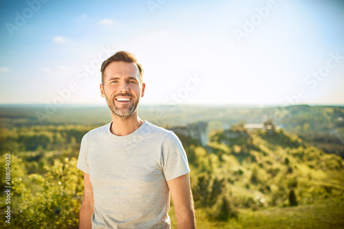 Obraz Portrait of man smiling at camera while on trip in the mountains - fototapety do salonu