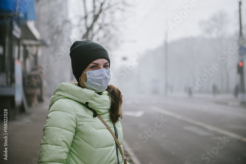 Fotografía the girl is standing by the road in a protective medical mask.