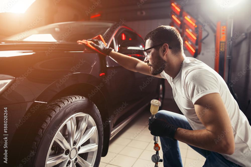 Obraz A man cleaning car with microfiber cloth, car detailing or valeting concept. Selective focus. fototapeta, plakat