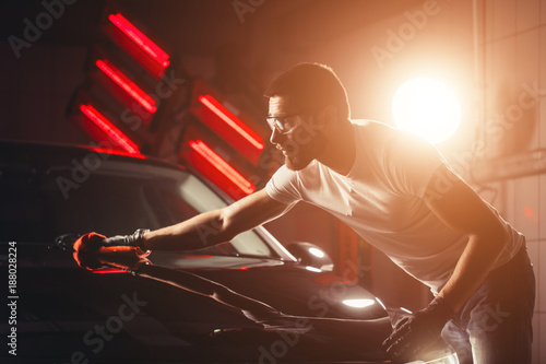 Fototapeta A man cleaning car with microfiber cloth, car detailing or valeting concept. Selective focus. obraz