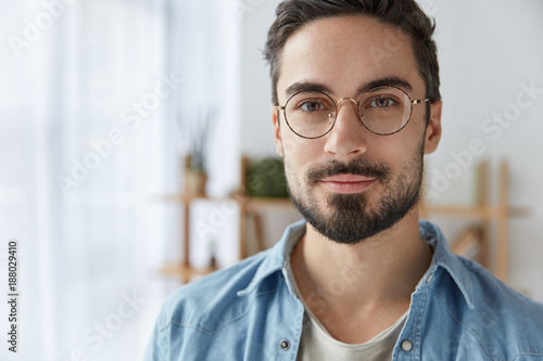 Fotografía  Close up portrait of handsome bearded man wears round spectacles, has appealing appearance with beard and mustache, dressed in fashionable clothes, stands against cozy interior