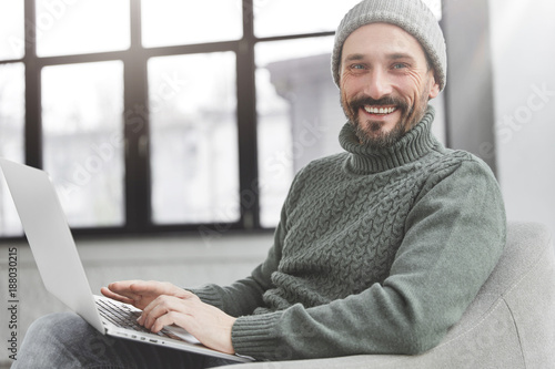 Smiling middle aged male enterpreneur checks corporate balance, makes money transfer online, works on modern laptop computer, connected to wireless internet. Blogger reads news on social networks