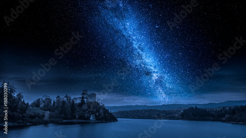 Beautiful castle by the lake at night with milky way