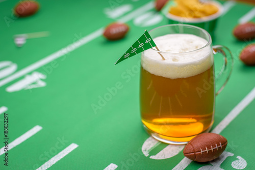 large glass mug of cold beer on table with superbowl party decorations Canvas Print