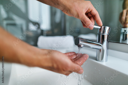 Cuadros en Lienzo  Man washing hands in bathroom sink at home checking temperature touching running water with hand