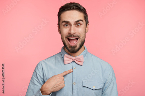 Fotografía  Puzzled young male model indicates at himself with indignant expression, demonstrates new bowtie, isolated over pink background