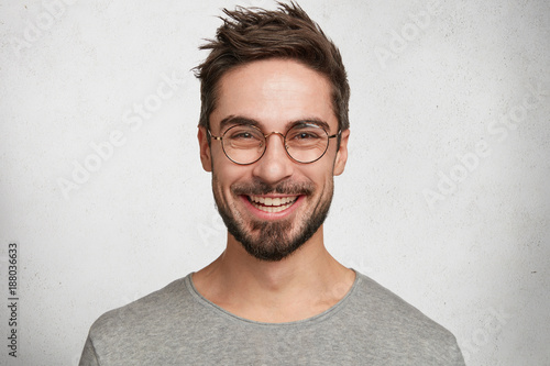 Fotografie, Obraz  Headshot of satisfied cheerful handsome man grins at camera, glad to find suitable well paid job, isolated over white concrete background