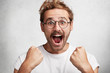 canvas print picture - Excited happy man screams with happiness, celebrates his great triumph and victory, clenches fists, can`t believe in success, says: Wow, how great it is! Male champion achieves big effective results