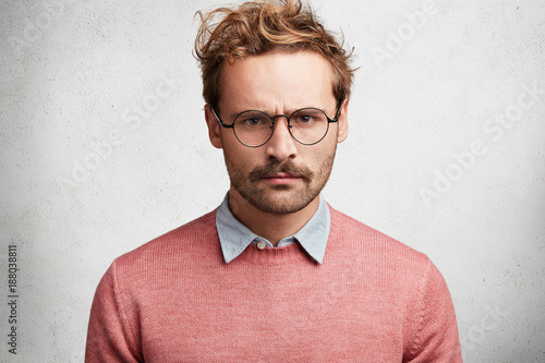 Valokuva  Horizontal shot of grumpy angry man frowns face in dissatisfaction, looks through spectacles, has gloomy expression, poses against white concrete background