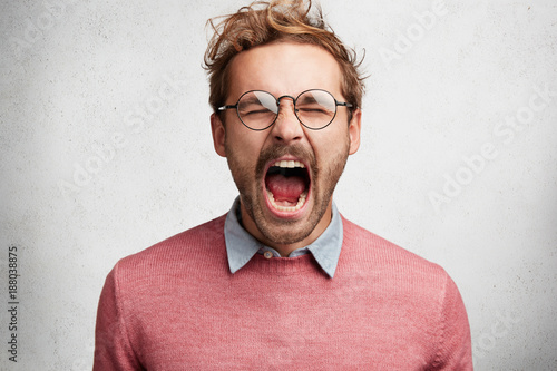 Fotografía  Emotional mad crazy young male screams loudly and with anger, being stressed and in panic, frowns face, isolated over white concrete wall